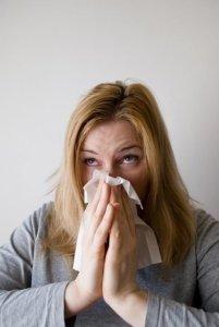 Frau in grauem Pullover putzt sich die Nase nach dem Gießen